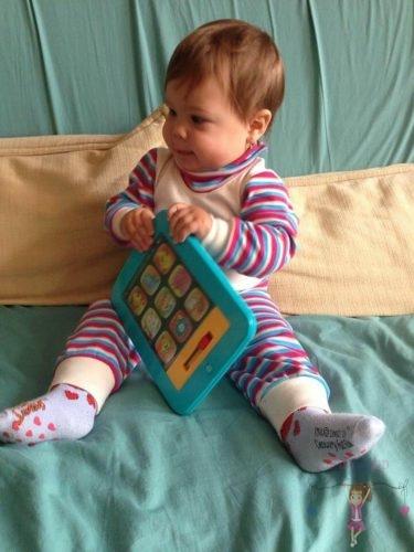 Babyandkidfashion, kislány ül az ágyon, az általunk készített babaruhában, kép.