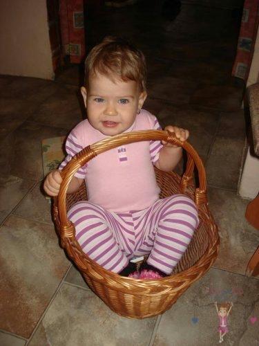 Babyandkidfashion, kislány ül a kosárban, az általunk készített babaruhában, kép.