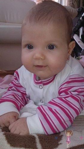 Babyandkidfashion, kislány hason fekszik a szőnyegen, az általunk készített babaruhában, kép.