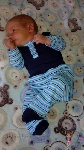 Babyandkidfashion, mosolygós kisfiú fekszik a kiságyban, az általunk készített babaruhában, kép.