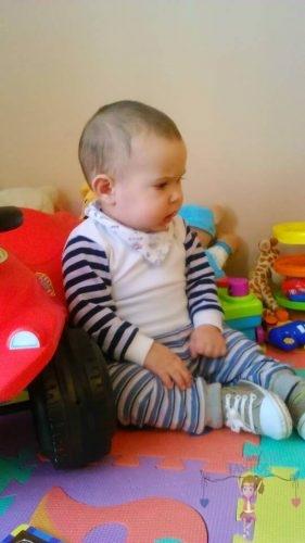 Babyandkidfashion, kisfiú a földön ül, az általunk készített babaruhában, kép.