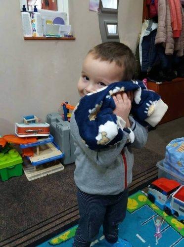 Babyandkidfashion, mosolygós kisfiú öleli a ruhát, az általunk készített babaruhában, kép.
