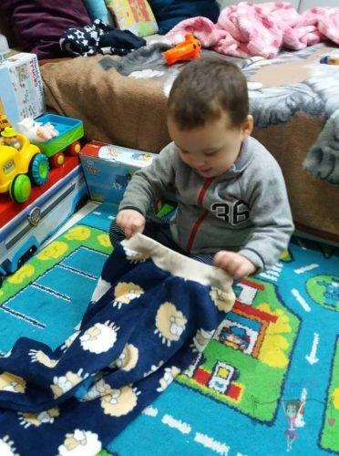 Babyandkidfashion, mosolygós kisfiú próbálja a ruhát, az általunk készített babaruhában, kép.