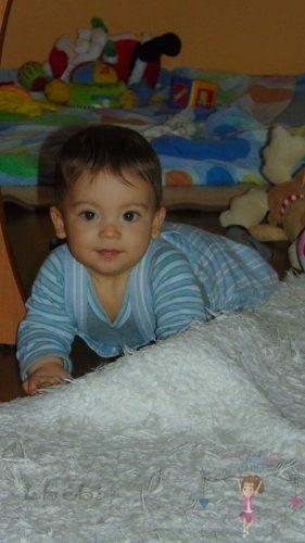 Babyandkidfashion, cuki kisfiú mászik a földön, az általunk készített babaruhában, kép.