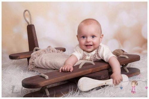 Babyandkidfashion, cuki kisfiú ül a földön, az általunk készített babaruhában, kép.