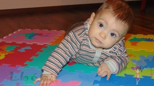 Babyandkidfashion, cuki kisfiú hason fekszik a földön, az általunk készített ruhában, kép.