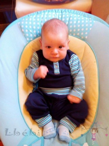 Babyandkidfashion, cuki kisfiú ül a gyerekülésben, az általunk készített ruhában, kép.