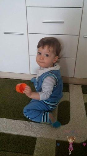Babyandkidfashion, cuki kisfiú ül a szőnyegen, az általunk készített ruhában, kép.