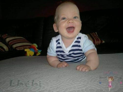 Babyandkidfashion, mosolygós kisfiú fekszik az ágyban, az általunk készített ruhában, kép.