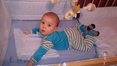 Babyandkidfashion, kisbaba fekszik a kiságyban, az általunk készített ruhában, kép.
