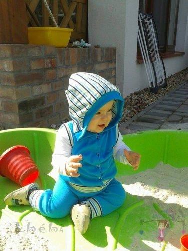 Babyandkidfashion, kisfiú ül a homokozóban, az általunk készített ruhában, kép.