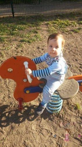Babyandkidfashion, kisbaba a játszótéren ülve, az általunk készített ruhában, kép.