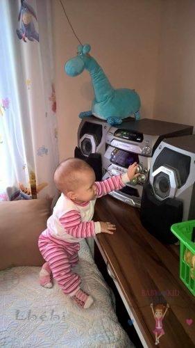 Babyandkidfashion, kisbaba játszik, az általunk készített ruhában, kép.