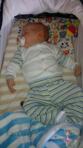 Babyandkidfashion, kisbaba fekszik a kiságyban, az általunk készített fiú ruhában, kép.