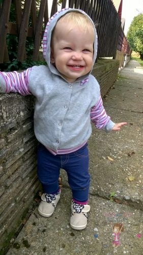 Babyandkidfashion, mosolygós kislány áll a járdán, az általunk készített ruhában, kép.
