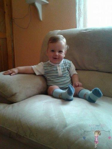 Babyandkidfashion, kisbaba ül az ülőgarnitúrán, az általunk készített fiú ruhában, kép.