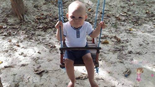 Babyandkidfashion, kisbaba hintázik, általunk készített fiú ruhában, kép.
