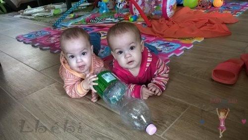 Babyandkidfashion, kislány iker babák fekszenek a földön, általunk készített ruhában, kép.