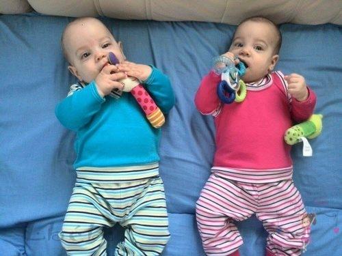 Babyandkidfashion, iker babák fekszenek az ágyon, általunk készített ruhában, kép.