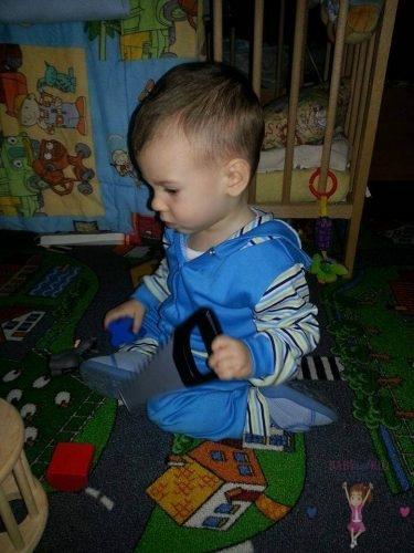Babyandkidfashion, kisfiú játszik a szőnyegen, általunk készített fiú ruhában, kép.