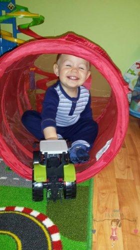 Babyandkidfashion, mosolygós kisfiú játszik a mászóalagútban, kép.