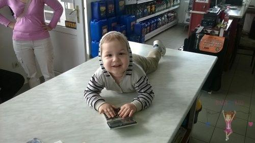 Babyandkidfashion, mosolygós kisfiú a boltban, az általunk készített babaruhában, kép.