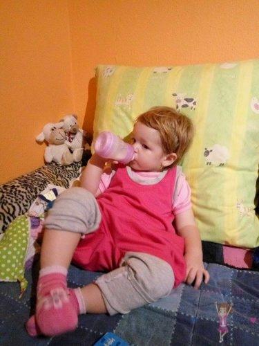 Babyandkidfashion, aranyos kislány cumisüvegből iszik az ágyon fekve, az általunk készített babaruhában, kép.