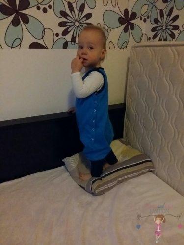 Babyandkidfashion, aranyos kisfiú áll az ágyon, az általunk készített babaruhában, kép.