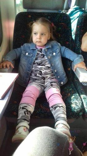 Babyandkidfashion, aranyos kislány ül a vonaton, az általunk készített babaruhában, kép.
