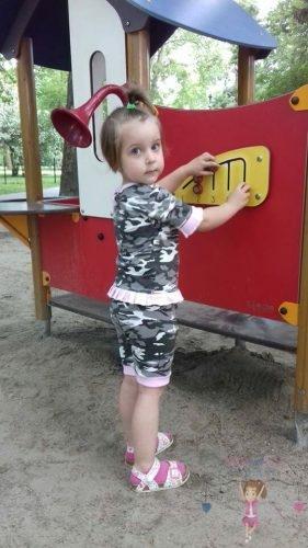 Babyandkidfashion, aranyos kislány áll a játszótéren, az általunk készített babaruhában, kép.