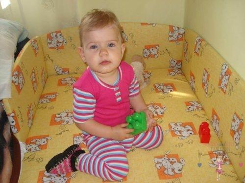 Babyandkidfashion, aranyos kislány ül a kiságyban, az általunk készített babaruhában, kép.