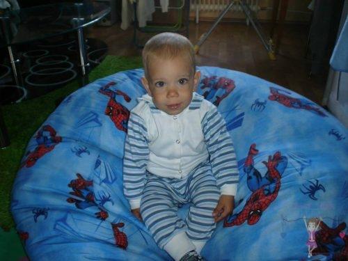 Babyandkidfashion, aranyos kisfiú ül az babzsákon, az általunk készített babaruhában, kép.