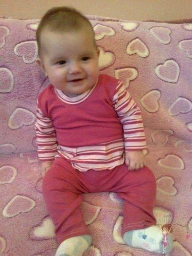 Babyandkidfashion, aranyos kislány ül az ágyon, az általunk készített babaruhában, kép.