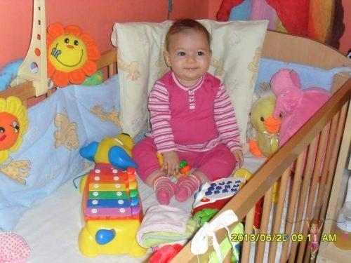 Babyandkidfashion, aranyos kislány ül a kiságyon, az általunk készített babaruhában, kép.