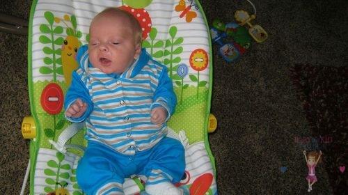 Babyandkidfashion, kisfiú fekszik a babahordozóban, az általunk készített babaruhában, kép.