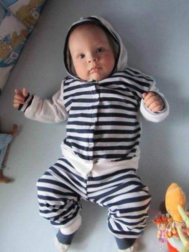 Babyandkidfashion, kisfiú fekszik az ágyon, az általunk készített babaruhában, kép.