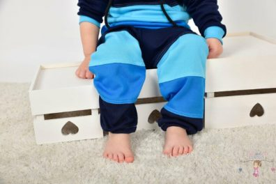Ládán csücsülő kisfiú, kék színű variációkkal lévő nadrágban, kép.
