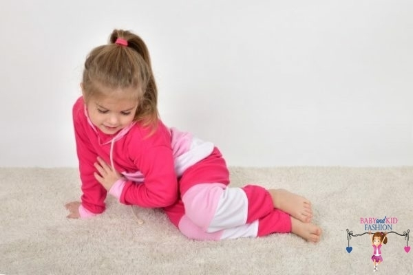 Szőnyegen fekvő kislány, rózsaszín színek variációjából készült kapucnis szettben, kép.