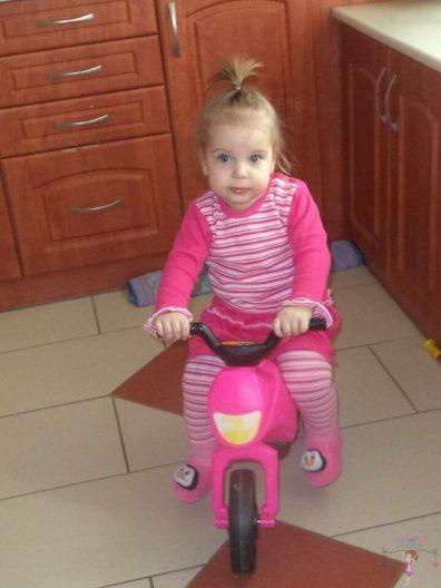 Babyandkidfashion, kislány ül a kismotoron, az általunk készített babaruhában, kép.