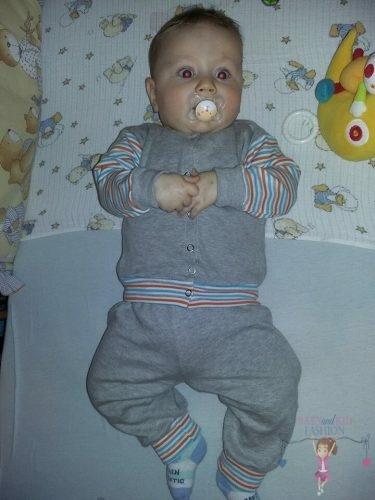 Babyandkidfashion, cuki kisbaba fekszik a kiságyban, az általunk készített babaruhában, kép.