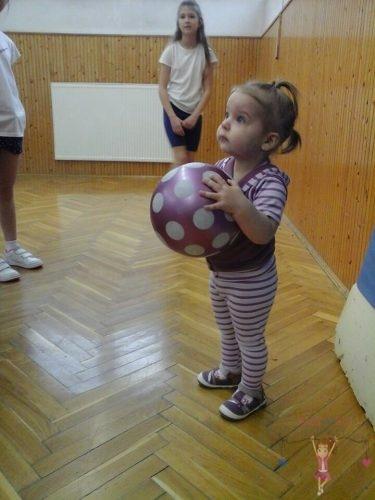 Babyandkidfashion, kislány áll labdával a kezébe a tornateremben, az általunk készített babaruhában, kép.
