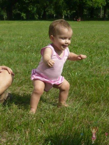 babyandkidfashion, mosolygós kisbaba áll a fűben, kép.