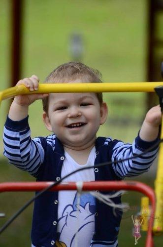 babyandkidfashion, mosolygós kisbaba áll a játszótéren, kép.