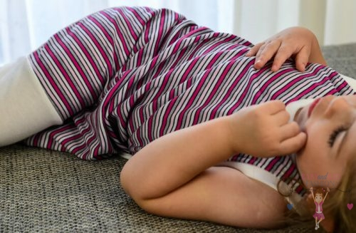 babyandkidfashion tipegő hálózsák, rózsaszín csíkos, fekvő kislányon, kép.