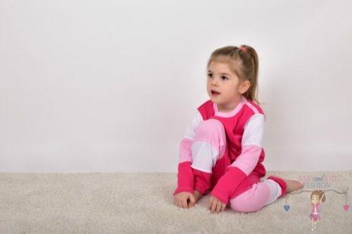 Szőnyegen ülő kislány, rózsaszín színek variációjából készült két részes szettben, kép.