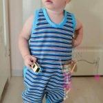 babyandkidfashion tipegő hálózsák kisfiún, kék csíkos tipegő hálózsákban, egy kisautóval játszó kisbabán, kép.