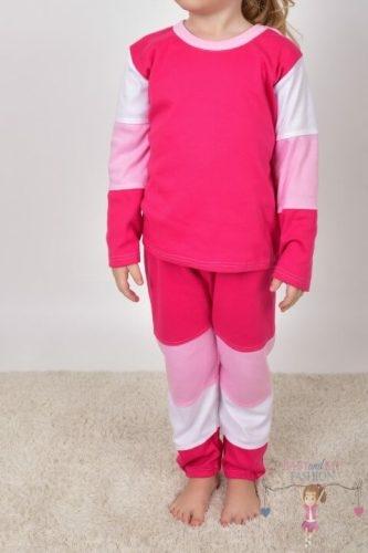 Szőnyegen álló kislány, rózsaszín színek variációjából készült két részes szettben, kép.