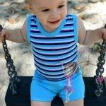 babyandkidfashion kisfiú kék csíkos bodyban hintázik, kép.