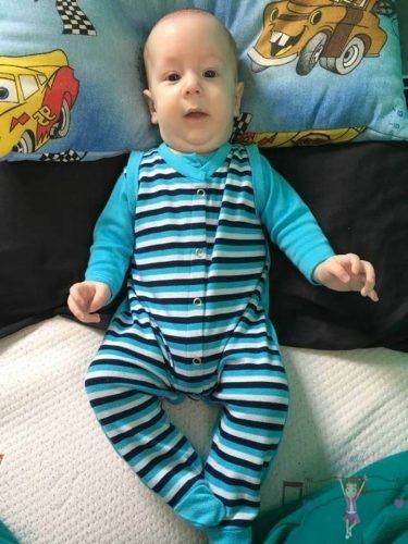 rugdalózó szerepe a hétköznapokban, egy mosolygós kisfiú baba, hosszú ujjú rugi, talppal, türkiz színű ujjal. A rugdalózó fiús színű sötétkék-türkizkék csíkos, kép.