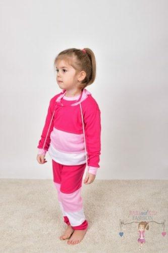 Szőnyegen álló kislány, rózsaszín színek variációjából készült kapucnis szettben, kép.